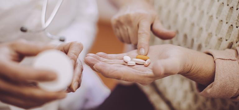 osoba trzymająca tabletki